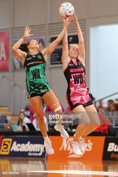 Verity Charles of the Fever and Emily Burgess of the Thunderbirds compete in the air during the round one Super Netball match between the...