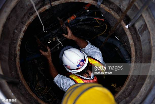 Verizon employees enter a manhole in the Wall Street area near the World Trade Center terrorist attack site