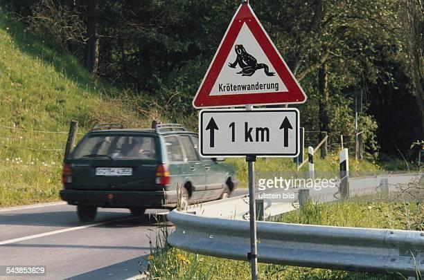 Verkehrsschild zur Anzeige dass über eine Strecke von einem Kilometer mit dem verstärktem Auftreten von Kröten auf der Fahrbahn zu rechnen ist...