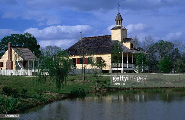 """vermillionville cajun village church.   a """"living history museum"""" , vermillionville is on 23 acres of park land with walkways which lead you through the acadian village-style houses and  craft shops. cajun cooking is demonstrated and cajuns bands perform. - lafayette louisiana stock pictures, royalty-free photos & images"""