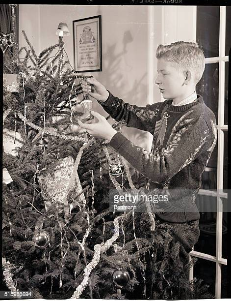 A boy hangs an ornament on a Christmas tree Undated photograph