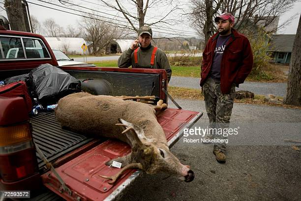 A Vermont state wildlife biologist not shown records the data from a recently shot whitetail deer as the hunter Ron Daniels center and his hunting...