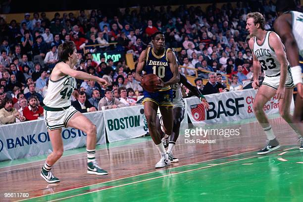Vern Fleming of the Indiana Pacers drives to the basket against Danny Ainge and Larry Bird of the Boston Celtics during a game played in 1985 at the...