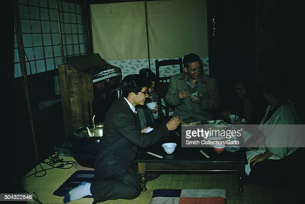 Vernacular snapshot of people kneeling around a straw mat in a Japanese home Japan 1951