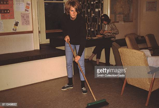 Vernacular snapshot photograph of woman sweeping the floor of a youth hostel 1961