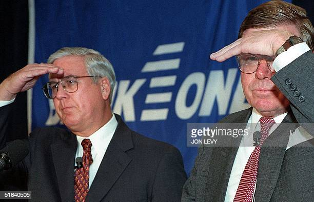 Verne Istock CEO of First Chicago NBD and John McCoy CEO of Banc One shield their eyes from bright lights 13 April at a press conference in New York...