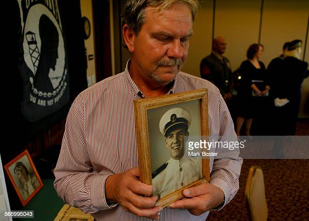 Verne J Rainey holds a portrait of his uncle missing World War II USMC pilot First Lt Laverne Lallathin whose remains were recently recovered before...