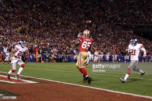 Vernon Davis of the San Francisco 49ers catches a 28yard touchdown pass in the third quarter against Corey Webster of the New York Giants during the...