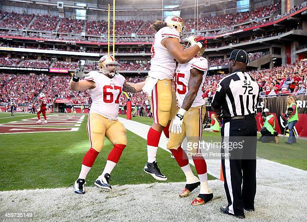Vernon Davis of the San Francisco 49ers celebrates with his teammates after scoring a 3 yard touchdown pass from Colin Kaepernick against the Arizona...
