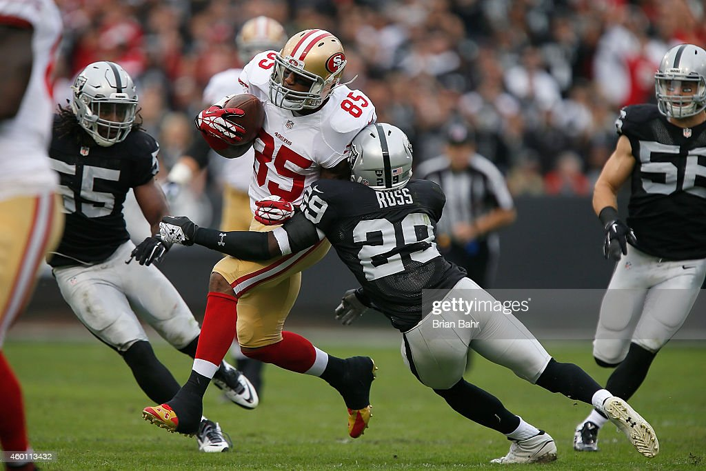 Vernon Davis #85 of the San Francisco 49ers gets past Brandian Ross #29 of the Oakland Raiders in the first quarter at O.co Coliseum on December 7, 2014 in Oakland, California.
