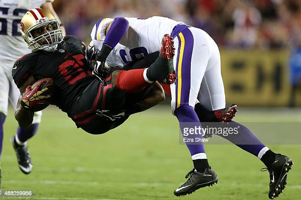 Vernon Davis of the San Francisco 49ers is tackled by Robert Blanton of the Minnesota Vikings after a catch during their NFL game at Levi's Stadium...