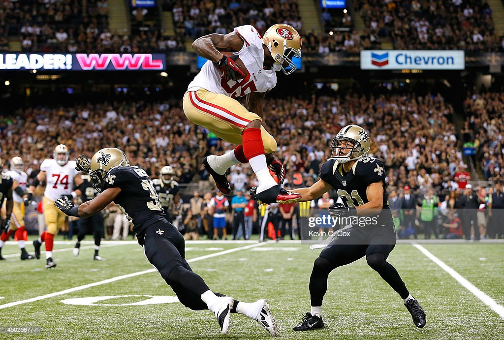 Vernon Davis #85 of the San Francisco 49ers leaps over Jabari Greer #33 and Chris Carr #31 of the New Orleans Saints at Mercedes-Benz Superdome on November 17, 2013 in New Orleans, Louisiana.