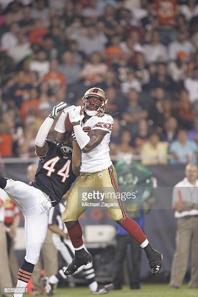 Vernon Davis of the San Francisco 49ers makes a reception against Kevin Payne of the Chicago Bears at Soldier Field during the NFL game on August 21...