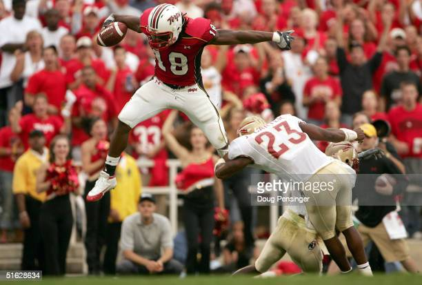 Vernon Davis of the University of Maryland Terrapins leaps over the defense of Bryant McFadden and Jerome Carter of the Florida State Seminoles...