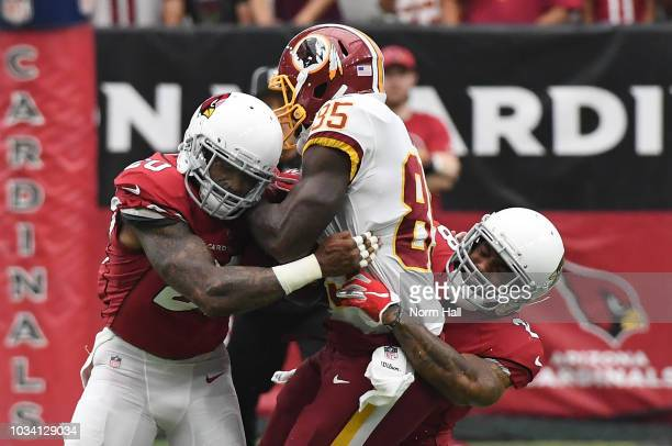Vernon Davis of the Washington Redskins is tackled by Deone Bucannon and Jamar Taylor of the Arizona Cardinals at State Farm Stadium on September 9,...