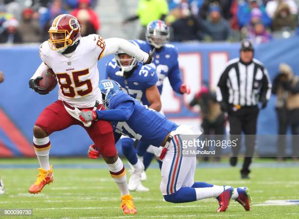 Vernon Davis of the Washington Redskins runs with the ball while Darian Thompson of the New York Giants attempts to tackle him during the first half...