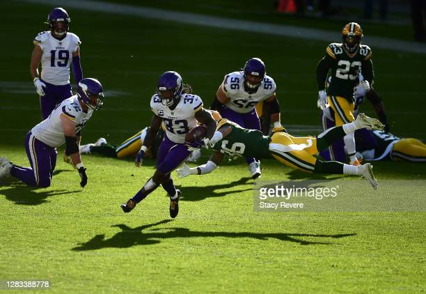 Vernon Scott of the Green Bay Packers misses the tackle on Dalvin Cook of the Minnesota Vikings as he scores during the third quarter of the game at...