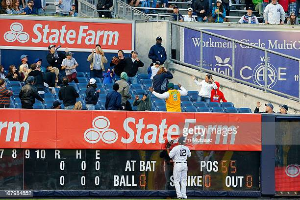 Vernon Wells of the New York Yankees stands at the wall after the first pitch of the game hit by Adam Rosales of the Oakland Athletics lands in the...