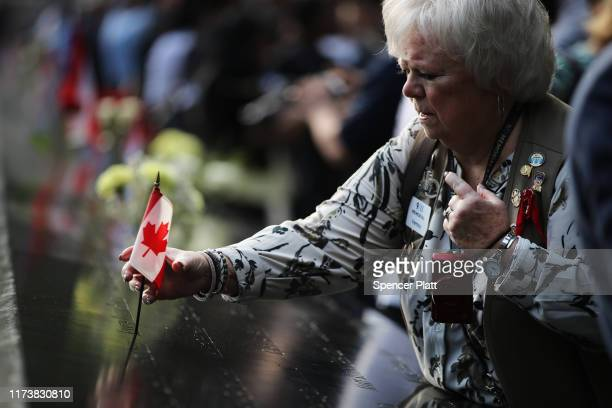 Vernoy Paolini places a Canadian flag in the name of a Canadian victim of the September 11 terrorist attacks at the National September 11 Memorial...