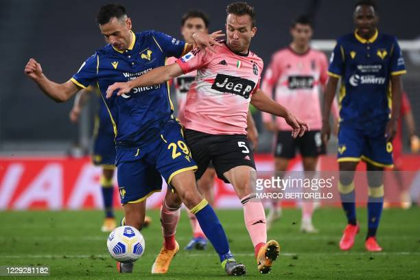 Verona's Croatian forward Nikola Kalinic fights for the ball with Juventus' Brazilian midfielder Arthur during the Italian Serie A football match...