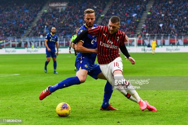 Verona's Kosovan defender Amir Rrahmani tackles AC Milan's Croatian forward Ante Rebic during the Italian Serie A football match AC Milan vs Verona...