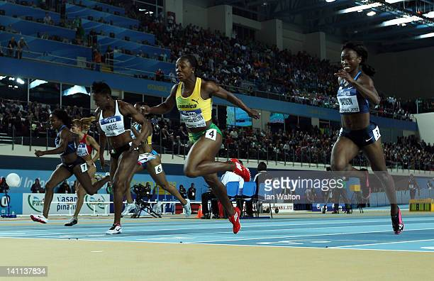 Veronica Campbell-Brown of Jamaica crosses the line to win gold ahead of silver medalist Murielle Ahoure of the Ivory Coast bronze medalist Tianna...
