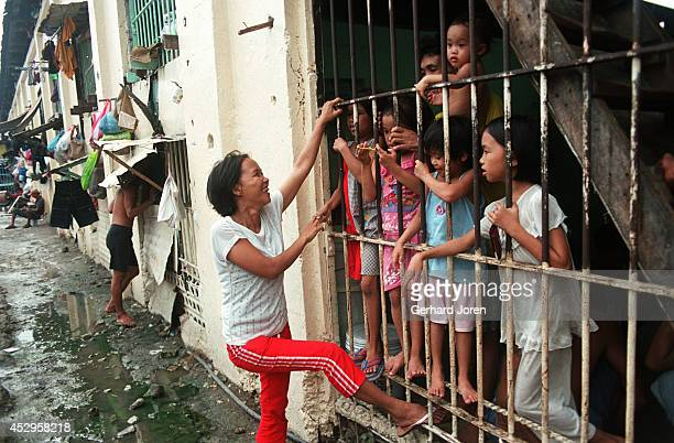 Veronica Delacruz talks with her husband Jaime and their kids at their cell barrack at Manila City Jail. Jaime is a member of Batang City Jail, one...