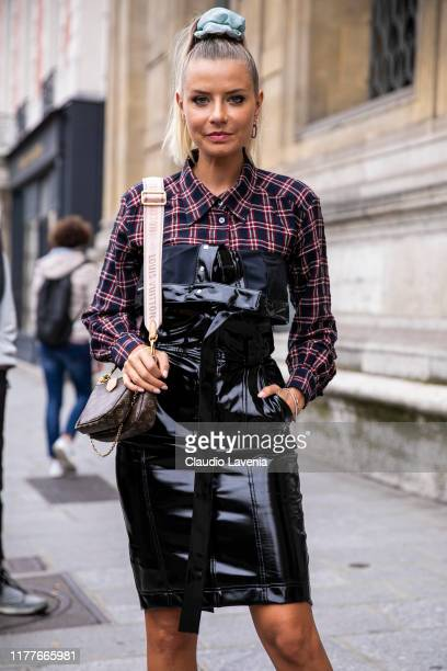 Veronica Ferraro, wearing a checked shirt, black vynil mini dress and Louis Vuitton bag, is seen outside the Unravel show during Paris Fashion Week -...