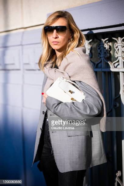 Veronica Giomini wearing a grey blazer cream sweater and white bag is seen outside the MSGM show during the Milan Men's Fashion Week on January 12...