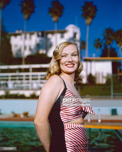 Veronica Lake US actress smiling as she poses beside a swiming pool wearing a redandwhite striped swimsuit circa 1950