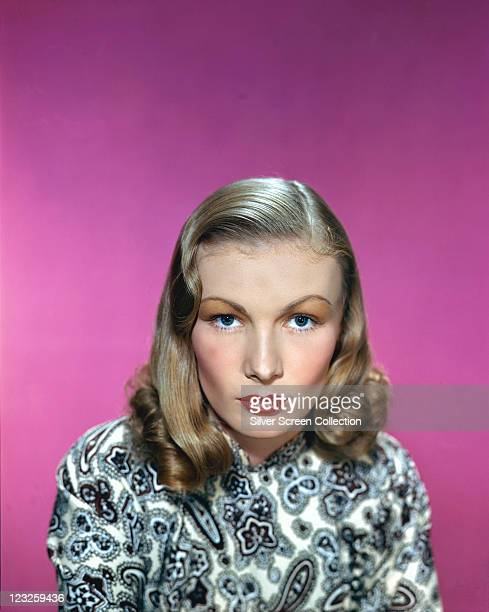 Veronica Lake US actress wearing a blueandwhite paisley pattern top in a studio portrait against a cerise background circa 1955