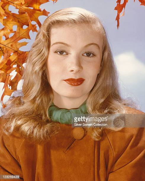 Veronica Lake US actress wearing a tan coloured suede coat with a large button in a studio portrait against a background of cloudy skies and autumnal...