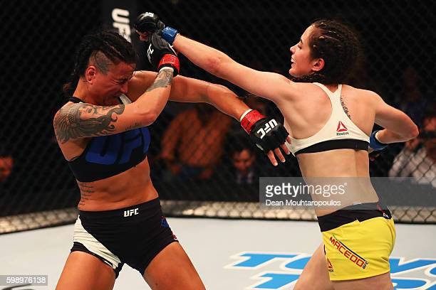 Veronica Macedo of Venezuela punches Ashlee EvansSmith of the USA compete in their Womens Bantamweight Bout during the UFC Fight Night held at...
