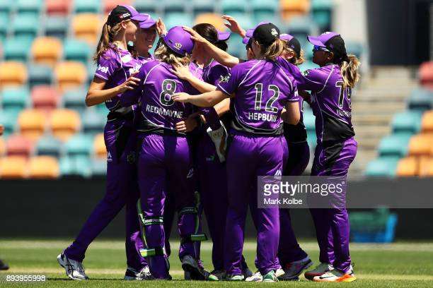 Veronica Pyke and Georgia Redmayne of the Hurricanes celebrate with their team after combining to take the wicket of Erin Burns of the Sixers during...