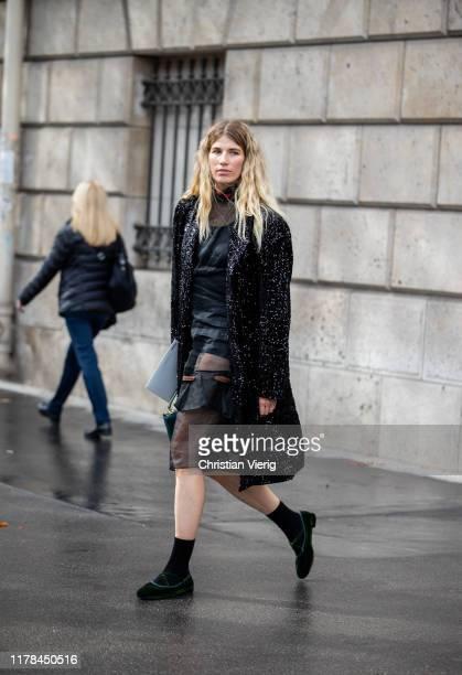 Veronika Heilbrunner seen wearing sheer dress, black coat outside Miu Miu during Paris Fashion Week Womenswear Spring Summer 2020 on October 01, 2019...