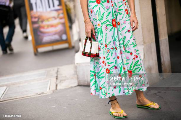 Veronika Heilbrunner wearing a floral print long dress mini white bag and yellow Havaianas is seen outside Schiaparelli show during Paris Fashion...