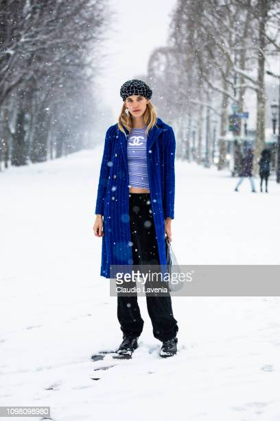 Veronika Heilbrunner, wearing a light blue Chanel top, black pants, blue coat, black shoes and checked hat, is seen outside Chanel show during Paris...