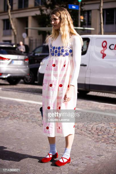 Veronika Heilbrunner, wearing a white turtleneck top, white decorated maxi dress, red flats and blue Miu Miu bag, is seen outside Miu Miu, during...