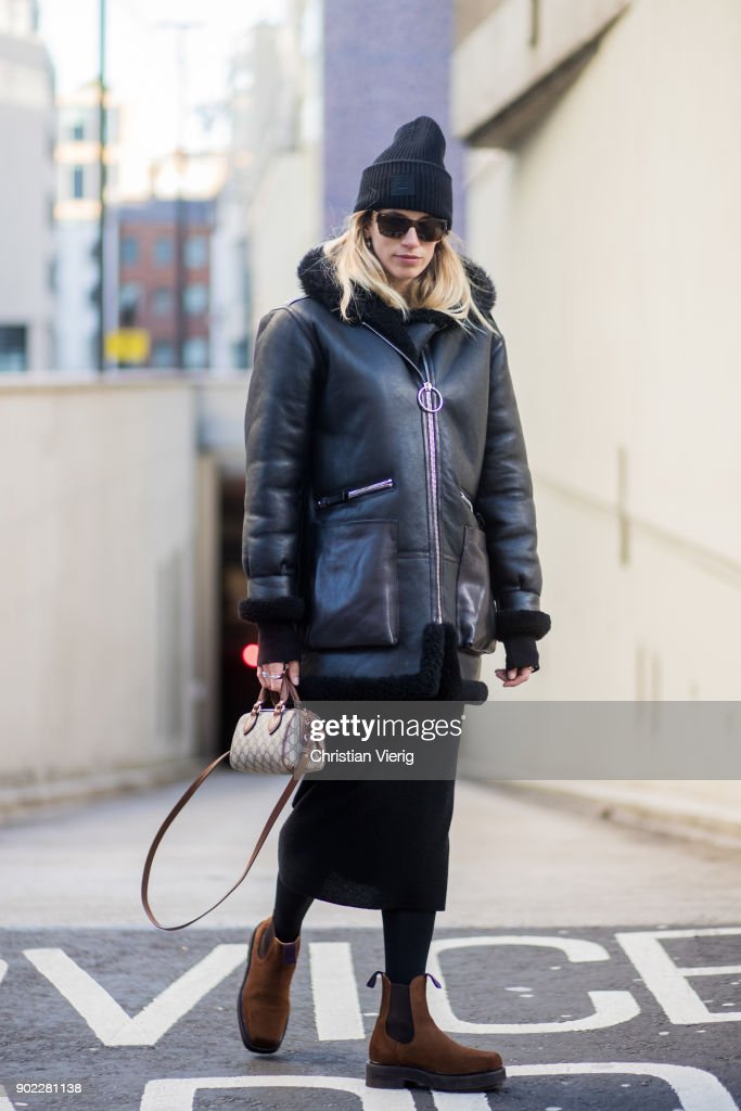 Veronika Heilbrunner wearing Gucci mini bag, Acne beanie, leather jacket, midi skirt, brown boots during London Fashion Week Men's January 2018 on January 7, 2018 in London, England.