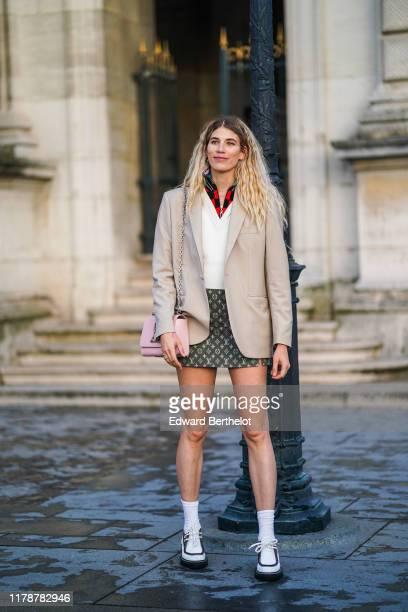 Veronika Heilbrunner wears a beige blazer jacket, a white v-neck pullover, a red and black checked shirt, a Vuitton monogram skirt, white socks,...