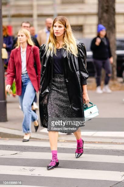 Veronika Heilbrunner wears a black leather coat, a skirt, pink socks, black shoes, outside Miu Miu, during Paris Fashion Week Womenswear...
