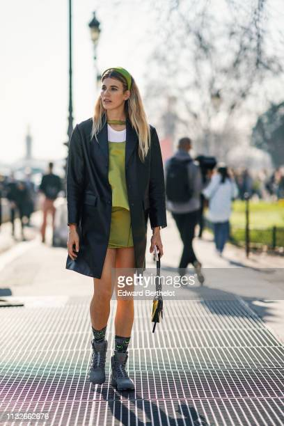 Veronika Heilbrunner wears a headband a leather long jacket a green dress boots outside Maison Margiela during Paris Fashion Week Womenswear...