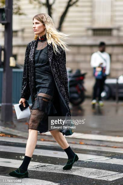 Veronika Heilbrunner wears a long black shiny glitter jacket a black mesh silky lustrous dress with ruffle collar a green bag black socks shoes...
