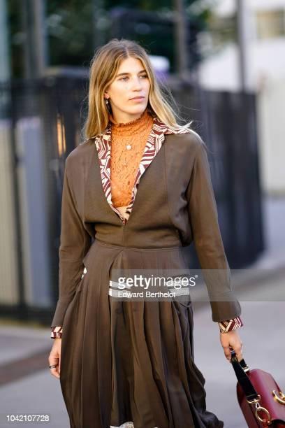 Veronika Heilbrunner wears a pleated khaki dress a brown Chloe bag white socks and shoes an orange turtleneck outside Chloe during Paris Fashion Week...