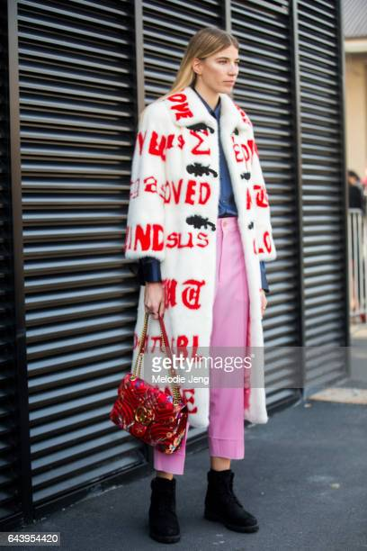 Veronika Heilbrunner wears a white Gucci fur coat with text and a red Gucci bag outside the Gucci show during Milan Fashion Week Fall/Winter 2017/18...
