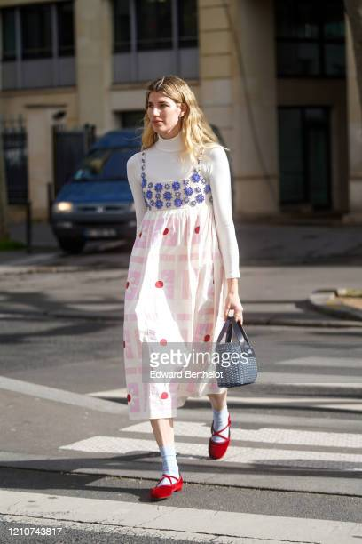 Veronika Heilbrunner wears a white turtleneck pullover, a bejeweled and floral print colored dress, gray socks, red shoes, a bag, outside Miu Miu,...