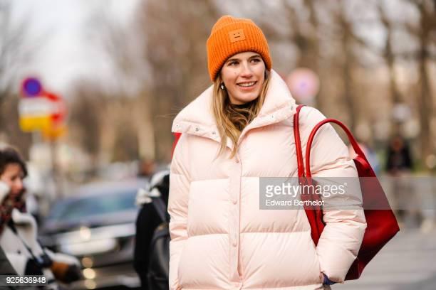 Veronika Heilbrunner wears an orange beanie hat a pink puffer coat during Paris Fashion Week Womenswear Fall/Winter 2018/2019 on February 28 2018 in...