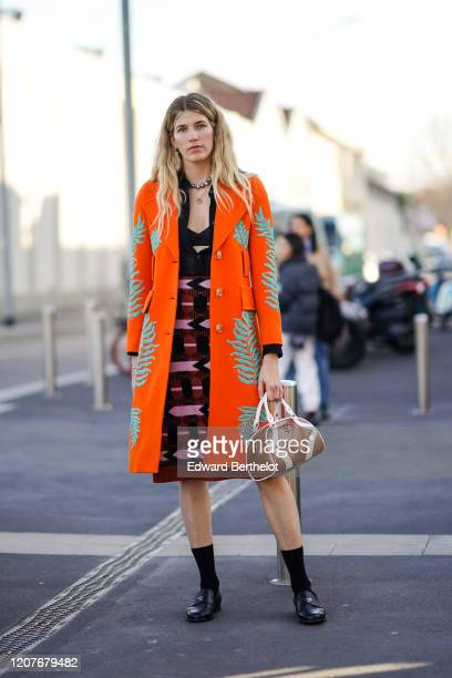 Veronika Heilbrunner wears an orange long coat, a pink and purple dress, a brown leather Prada bag, black socks, black leather shoes, outside Prada,...