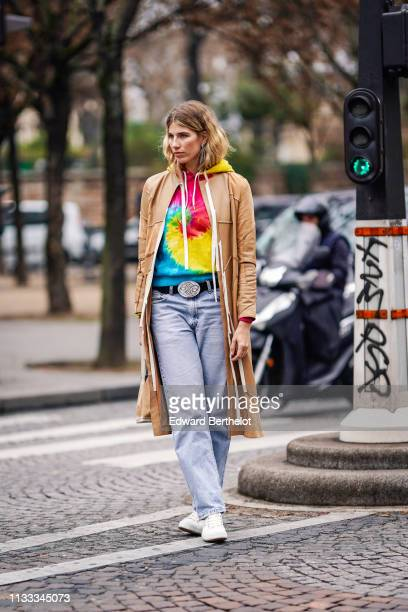 Veronika Heilbrunner wears earrings a colorful hooded sweatshirt a camel leather trench coat a camel suede handbag jeans white sneakers outside...