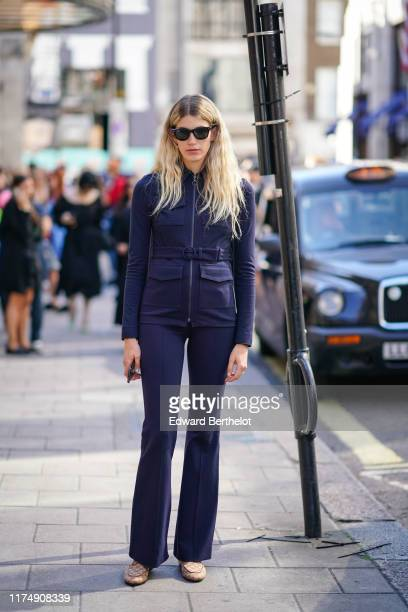 Veronika Heilbrunner wears sunglasses, a navy blue jacket, flare pants, during London Fashion Week September 2019 on September 15, 2019 in London,...